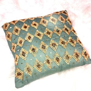 Turquoise pillow with wooden beads.